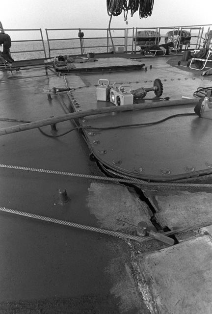 A close-up view of the crack in the starboard weather deck of the guided missile frigate USS SAMUEL B. ROBERTS (FFG-58) sustained when the ship struck a mine on April 14, 1988. The cables are part of damage control efforts to keep the crack from spreading