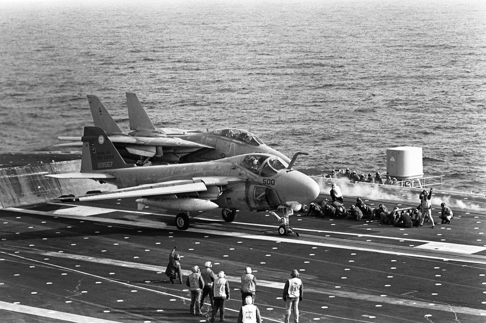 An A-6E Intruder aircraft of the Naval Air Test Center is launched from the flight deck of the aircraft carrier USS INDEPENDENCE (CV 62) as an F-14A Tomcat aircraft stands by