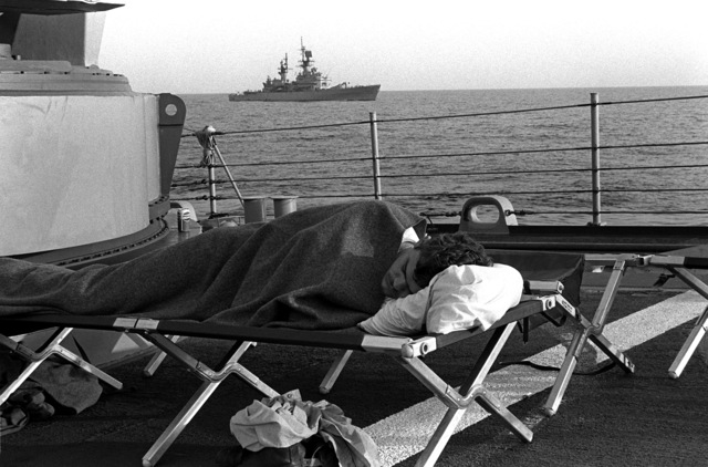 Fireman James Seward sleeps on the forecastle of the guided missile frigate SAMUEL B. ROBERTS (FFG-58). Some of the crew are sleeping on the deck because of hull damage sustained when the ship struck a mine on April 14, 1988. The guided missile cruiser USS JOUETT (CG-29) is in the background