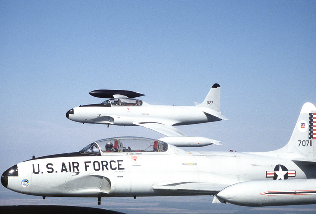 A left side view of two T-33 Shooting Star aircraft in flight. The further aircraft has been repainted and renumbered in anticipation of its delivery to the Mexican air force, to which it has been sold. The closer T-33 still belongs to the 95th Fighter In
