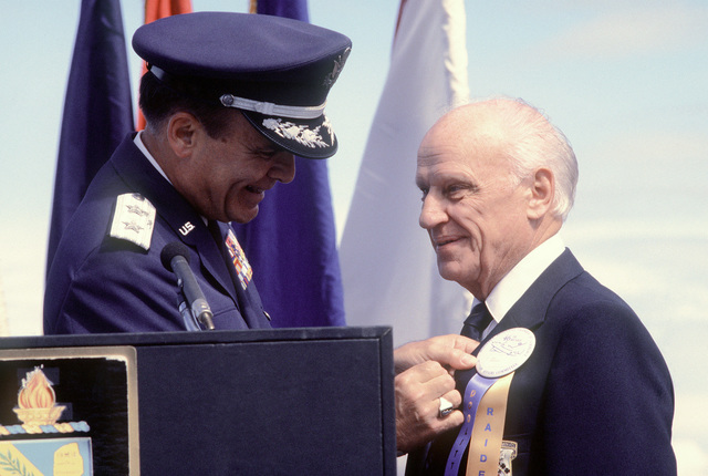Jacob D. DeShazer, one of Doolittle's Raiders, receives his POW/MIA medal for service in World War II from Major General Alexander K. Davidson, commander, 22nd Air Force, Military Airlift Command