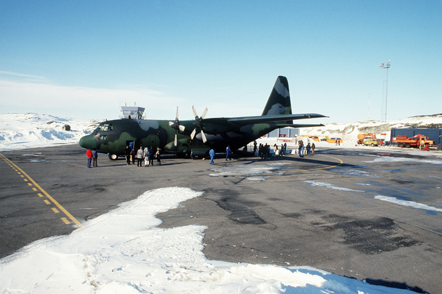 A C-130H aircraft from 109th Tactical Airlift Group of the New York Air National Guard waits for the first of the 230 Huskies bound for Thule Air Base in the north.  The dogs will then travel to the village of Quanaag, where the entire local population of