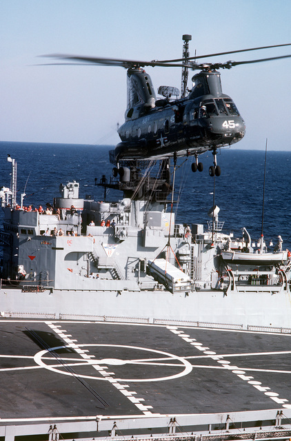 A Combat Support Squadron 8 (HC-8) CH-46 Sea Knight helicopter lifts ordnance from the fantail of the ammunition ship USS NITRO (AE-23) during a vertical replenishment with the aircraft carrier USS JOHN F. KENNEDY (CV-67). The amidships section of the frigate USS EDWARD MCDONNELL (FF-1043) is in the background