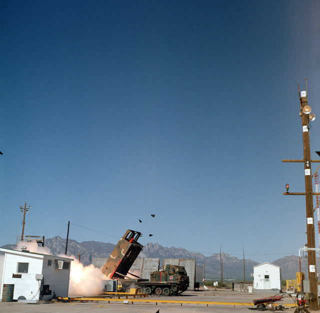 Smoke billows and fragments fly from a Multiple Launch Rocket System (MLRS) launcher as the nosecone of an Army Tactical Missile System (TACMS) missile emerges upon lift-off at Launch Complex 33
