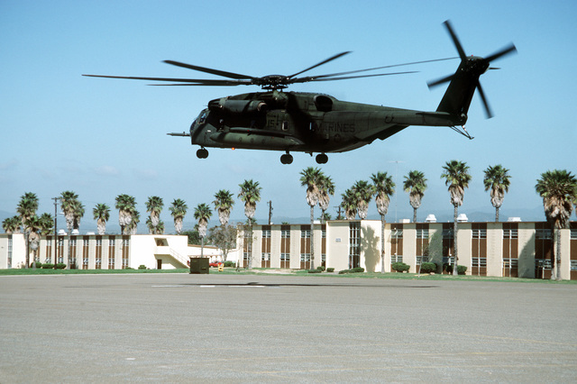 A CH-53E Super Stallion helicopter from Marine Heavy Helicopter Squadron 466 (HMH-466) descends to a landing zone on a parade deck behind a row of barracks at the combat center during Exercise Gallant Eagle '88