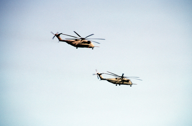 A pair of CH-53E Super Stallion helicopters from Marine Heavy Helicopter Squadron 466 (HMH-466) pass over the combat center during Exercise Gallant Eagle '88