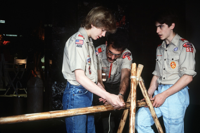 PETTY Officer First Class (PO1) Joseph E. Lawlis Jr. aids Boy Scouts as they tie a clove hitch for a fence, part of Troop 567's log cabin exhibit for Scout Expo 1988.  Lawlis is assigned to the nearby Naval Submarine Base, Bangor