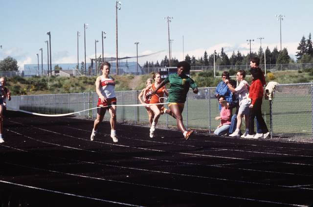 PETTY Officer Third Class (PO3) Rick L. Atkins, Lieutenant Junior Officer (LTJG) Kenneth V. Arneson, and other track officials clock in the winning runner at the Kitsap District Junior High Track and Field Championships.  Atkins and Arneson are assigned to the nearby Naval Submarine Base, Bangor