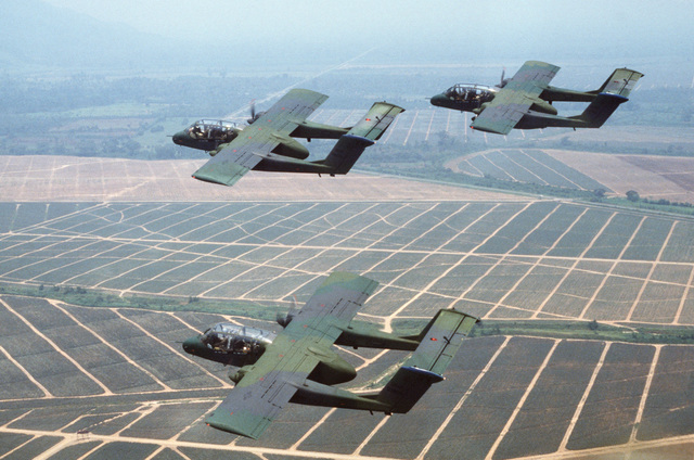 An air-to-air left side view of three 27th Tactical Air Support Squadron OV-10A Bronco aircraft flying in finger-tip formation over a Honduran farm.  The 27th TASS is deployed to Palmerola Air Base, Honduras, for a two-week joint training exercise with me