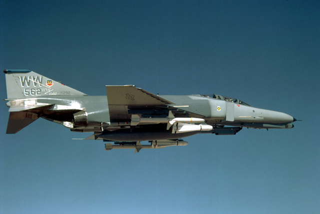 An air-to-air right side view of an F-4G Wild Weasel Phantom II aircraft from the 37th Tactical Fighter Wing. The aircraft is armed with two AGM-88 High-speed Anti-Radiation Missile (HARM) missiles, outboard stations, and two AGM-65A Shrike missiles, inbo