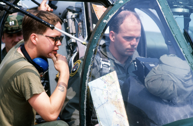 STAFF Sergeant (SSGT) Darrin Mooney, crew chief, and Lieutenant (LT) Robert Hughs, pilot, discuss an OV-10A Bronco console problem.  Both men are members of 27th Tactical Air Support Squadron which is deployed to Honduras for training