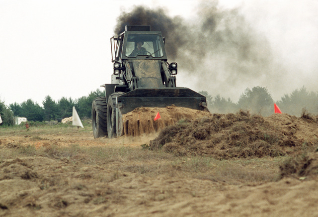 A Case W24C bulldozer moves dirt and sod while clearing an area for the tent city.  Members of the 823rd Civil Engineering Squadron are participating in a week-long field training and convoy security exercise