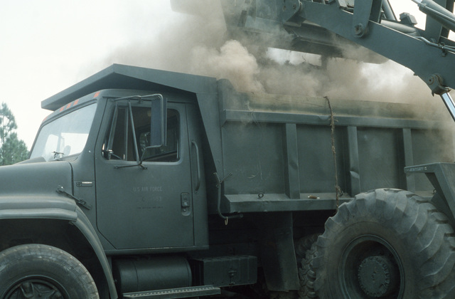 A Case W24C bulldozer unloads dirt into a dump truck during the 823rd Civil Engineering Squadron's week-long field training and convoy security exercise