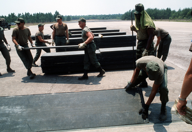 Members of the 823rd Civil Engineering Squadron unload runway repair plates during a week-long field training and convoy security exercise