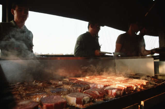 Steaks sizzle on a grill in a mobile kitchen trailer during the last day of the week-long field training and convoy security exercise conducted by members of the 823rd Civil Engineering Squadron