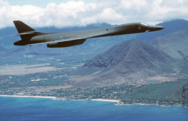 An air-to-air right side view of a B-1B aircraft in flight along the coastline of Hawaii during Exercise DISTANT MARINER.  The aircraft is returning from Guam during its first deployment to the Pacific