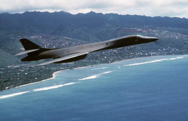 An air-to-air right side view of a B-1B aircraft in flight along the coastline during Exercise DISTANT MARINER