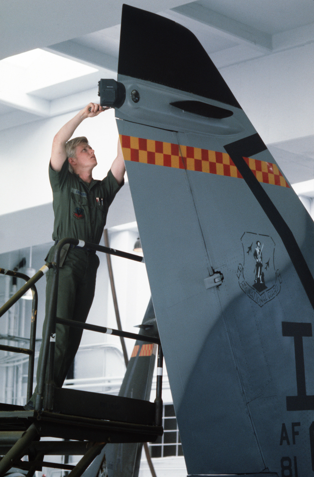 STAFF Sergeant (SSGT) David P. Cameron of the 124th Tactical Fighter Squadron, Iowa Air National Guard, changes the tail light bulb on an A-7D Corsair II aircraft during preparations for deployment to Yokota Air Base, Japan, to participate in Exercise COP