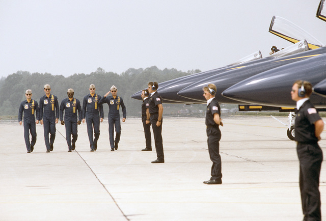 Flight crew members of the Navy's Blue Angel Flight Demonstration Team stand by as pilots approach their aircraft during the base open house