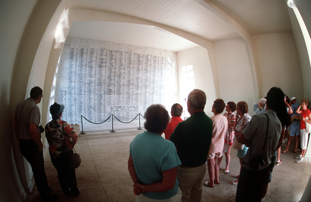 Visitors to the USS Arizona Memorial view a wall bearing the names of the sailors and Marines who died aboard the Arizona during the December 7, 1941, attack on Pearl Harbor