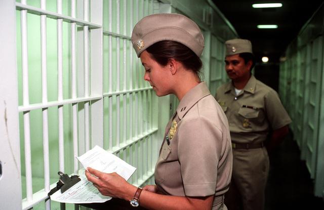 A female brig supervisor checks an inmate's records