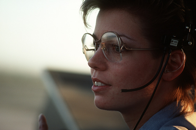 A female Navy air traffic controller uses headphones to communicate with pilots