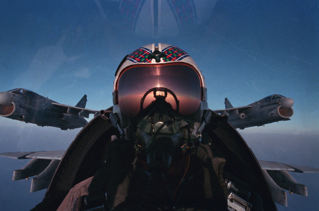 A self-portrait of Lieutenant Commander (LCDR) Leenhouts, pilot of an A-7 Corsair II of Attack Squadron 47 (VA-47), in the cockpit of his aircraft during deployment with the nuclear-powered aircraft carrier USS DWIGHT D. EISENHOWER (CVN 69).  Two other A-7E aircraft are in formation behind Leenhouts