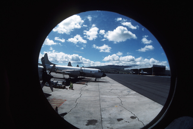 A view out the left side window of a P-3 Orion aircraft from Patrol Squadron 68 (VP-68) showing other P-3s parked on the flight line