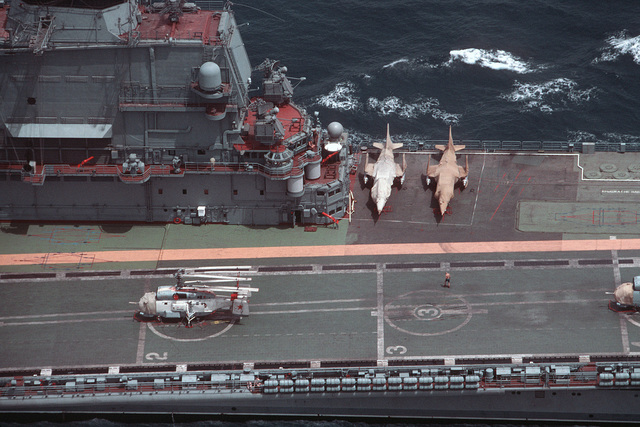 An aerial view of the aft portion of the island superstructure of the Soviet Kiev class VSTOL aircraft carrier BAKU (CVHG 103).  A Ka-27 Helix helicopter and covered Yak-36 Forger aircraft are parked on the flight deck
