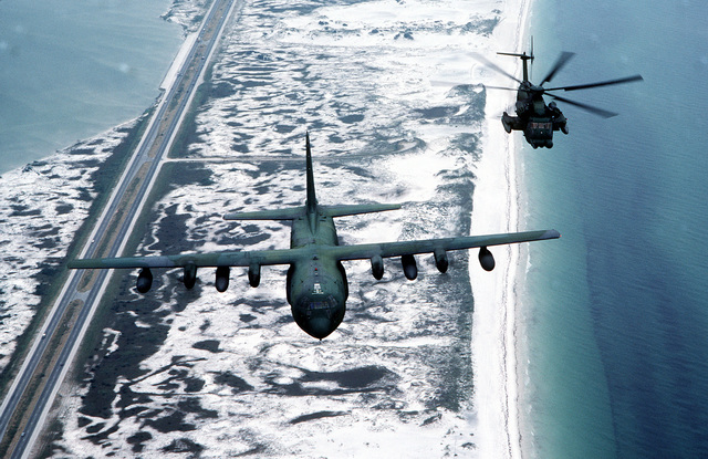 An air-to-air front overhead view of an MH-53H helicopter of the 20th Special Operations Squadron (SOS) and a C-130 Hercules of the 16th SOS over Hurlburt Field, FL