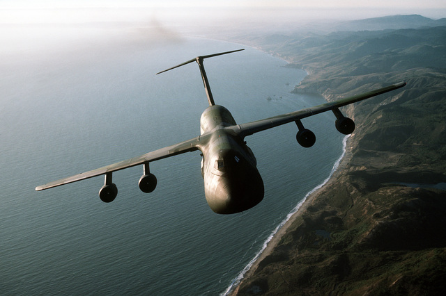 An air-to-air front view of a C-5B Galaxy aircraft from the 22nd Military Airlift Squadron in-flight over the coastline