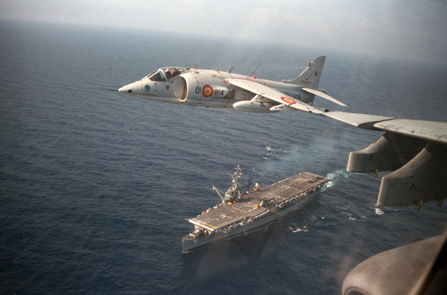 An air-to-air front view of a Spanish AV-8S Matador aircraft in flight over the Spanish aircraft carrier DEDALO (R01), below