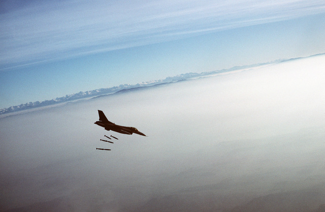 An air-to-air right side view of a 10th Tactical Fighter Squadron F-16C Fighting Falcon aircraft dropping Mark 82 500-pound bombs over the Bardenas-Reales Range during the weapons training deployment Exercise SABRE THUNDER
