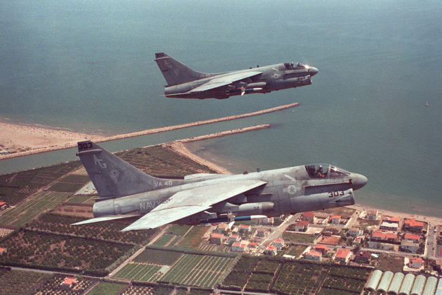 An air-to-air right side view of two Attack Squadron 46 (VA-46) A-7E Corsair II aircraft in flight over the coastline.  The aircraft are armed with AGM-45 Shrike missiles