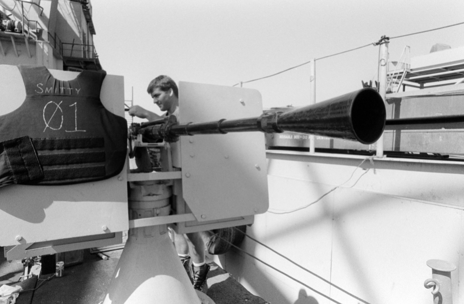 Quartermaster SEAMAN (SN) David Smith cleans a Mark 67 20 mm cannon mounted on the deck of a Special Boat Unit 20 PB Mark III patrol boat in the Persian Gulf