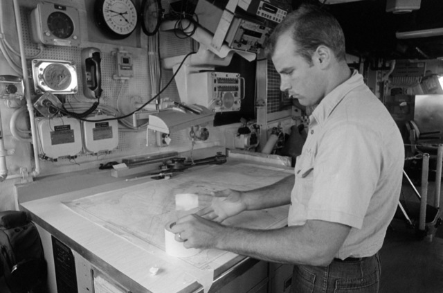 SEAMAN (SN) Roy Riker attaches a navigational chart of the Strait of Hormuz to the chart table on the bridge of the guided missile frigate USS NICHOLAS (FFG 47) in the Persian Gulf