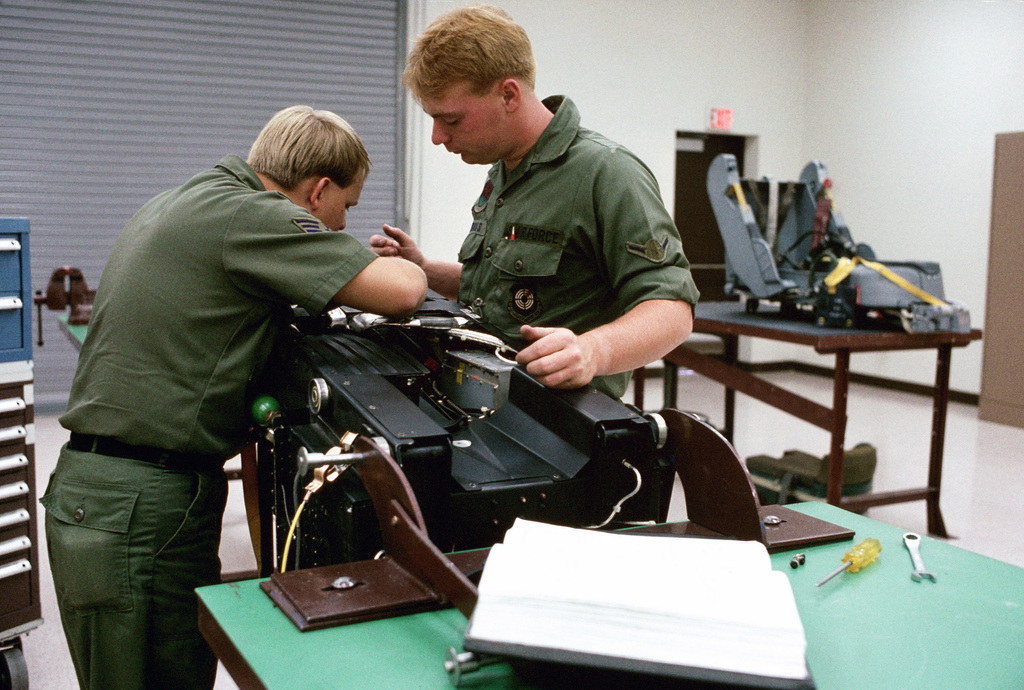 Sergeant (SGT) James W. Atherton and AIRMAN (AMN) Rodney L. Thomas remove an inertial reel initiator from an ACESII ejection seat.  Both men are members of the 57th Component Repair Squadron