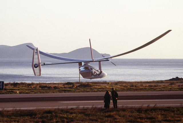 The Greek navy patrol boat HS Ipoploiarhos Troupakis (P-23) escorts Daedalus 88, a human-powered pedal plane, as it flies over the Aegean on its 74-mile trip between Crete and Santorini. The plane was built by students from the Massachusetts Institute of Technology and is being piloted by Greek national cycling champion Kanellos Kanellopolous. The flight was patterned after the Greek myth of Daedalus and his son, Icarus, who attempted to leave Crete by constructing wings with which to fly