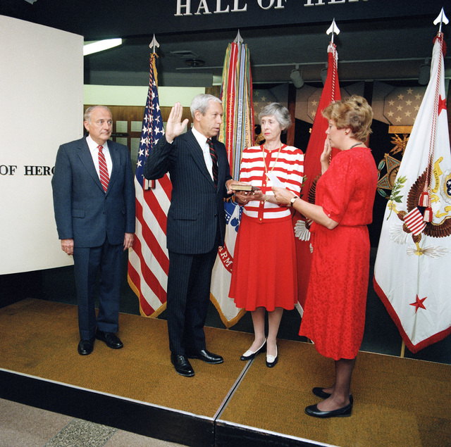 As his wife, Ann, holds the Bible, Michael P. W. Stone is sworn in as Undersecretary of the Army by Susan J. Crawford, General Counsel of the Army, during a ceremony at the Pentagon. Secretary of the Army John O. Marsh Jr. is at left