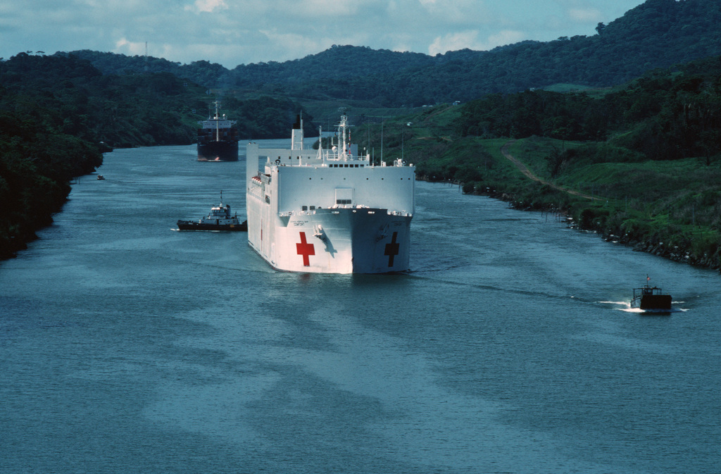 A starboard bow view of the hospital ship USNS COMFORT (T-AH 20) passing through Gaillard Cut.  The ship is transiting the Panama Canal en route to its home port of Baltimore.  The COMFORT, along with the hospital ship USNS MERCY (T-AH 19), is operated for the Navy by the Military Sealift Command