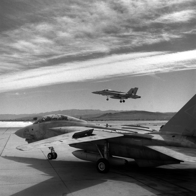 An F/A-18C Hornet aircraft of Strike Fighter Squadron 82 (VFA-82) lands, while an F-14A Tomcat of Fighter Squadron 102 (VF-102) prepares for takeoff during Carrier Air Wing 1 (CVW-1) strike training