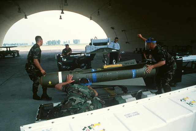 Airmen place an inert AGM-65 Maverick air-to-air missile on a cart with the aid of a weapons loader as an evaluator looks on. The airmen are participating in the missile breakout and assembly portion of the combat readiness competition Sabre Spirit '88. T