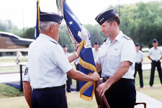 GEN Robert D. Russ, left, Commander in CHIEF, Tactical Air Command, passes the unit colors of the 12th Air Force (12th AF) to LGEN Peter T. Kempt during the 12th AF change of command. Kempf is relieving LGEN Merrill A. McPeak as Commander of the 12th AF
