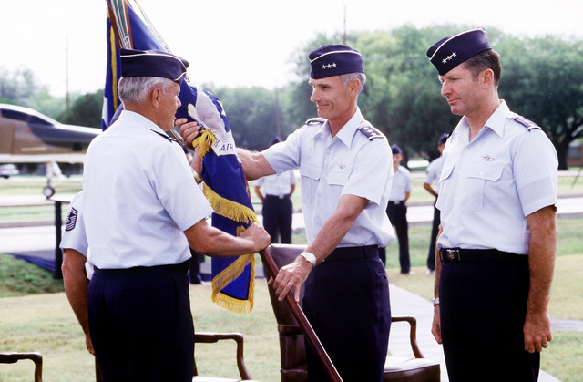 LGEN Merrill A. McPeak, center, passes the unit colors of the 12th Air Force (12th AF) to GEN Robert D. Russ, left, Commander in CHIEF, Tactical Air Command, during the 12th AF change of command. LGEN Peter T. Kempf, right, will assume command of the 12th AF from McPeak