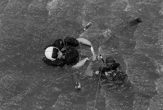 A diver assists an aircrewman into a survivor's sling so he can be hoisted aboard a helicopter during a Deep Water Environmental Survival Training (DWEST) class.  Forty Navy, Marine Corps, and Army pilots and aircrew personnel are participating in the last DWEST class to be conducted by the Fleet Aviation Specialized Operational Training Group, Pacific Fleet