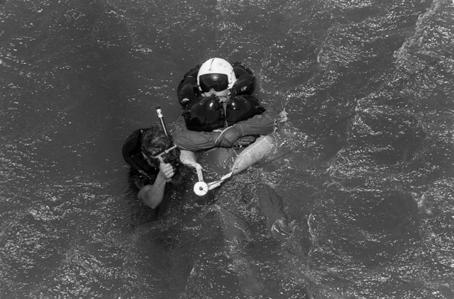 A diver assists an aircrewman into a survivor's sling so he can be hoisted aboard a Helicopter Anti-submarine Squadron 10 (HS-10) SH-3H Sea King helicopter during a Deep Water Environmental Survival Training (DWEST) class.  Forty Navy, Marine Corps, and Army pilots and aircrew personnel are participating in the last DWEST class to be conducted by the Fleet Aviation Specialized Operational Training Group, Pacific Fleet