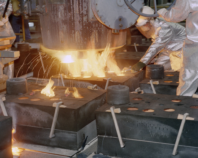 A workman pours molten metal into a no-bake mold at the old US Army Arsenal Foundry during Rearm III. This pour represents the last time that the old building, constructed in 1871, will be used