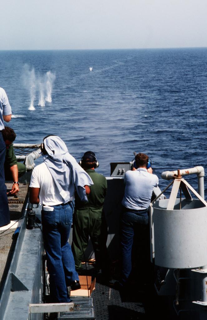 Crewmen fire an M2 .50-caliber machine gun from the fantail of the miscellaneous flagship USS CORONADO (AGF 11) in the Persian Gulf