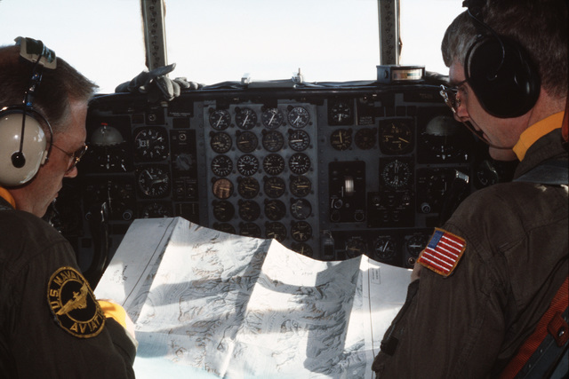 Commander (CDR) Rector, left, pilot of an Antarctic Development Squadron 6 (VXE-6) LC-130 Hercules aircraft, studies a chart of Scott Glacier with his copilot, Lieutenant Commander (LCDR) Monty Williams, while on a mission during Operation DEEP FREEZE