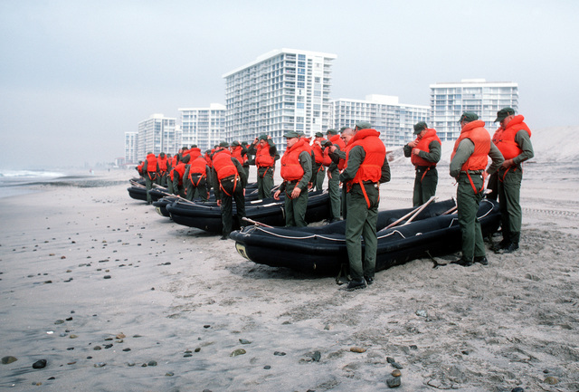 Students prepare to carry rubber rafts into the surf at Coronado Beach during Basic Underwater Demolition/SEAL (BUD/S) training